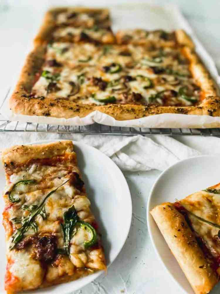 cooked no knead pan pizza dough in mushroom, sausage, and arugula pizza