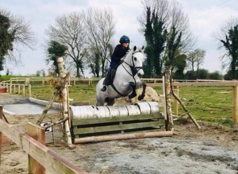 14'2 grey pony jumping a cross country fence made out of beer barrels. Fun and well jumped
