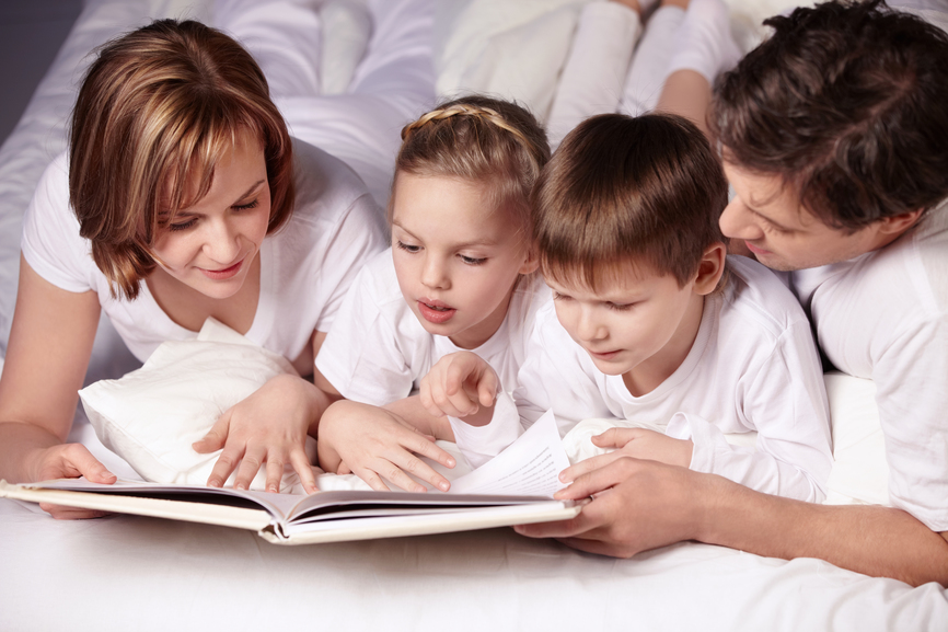 Parents of children reading a book in bed