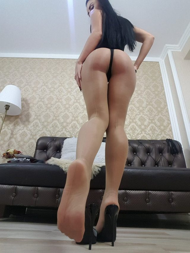 Goddess Ambra showing her ass and foot sole in tan pantyhose
