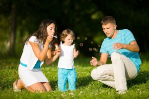 Happy Family making soap bubbles outdoors summer