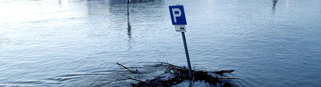 Parking sign in the middle of a flooded area. Flood insurance, flooded homes, Arizona Monsoon Season.