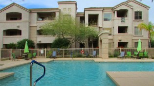 Crisp blue water in a beautiful neighborhood pool surrounded by three-story condominium buildings - 5303 N 7th St, Phoenix AZ - Sparkling neighborhood pool - Bill Salvatore, Arizona Elite Properties 602-999-0952 - Arizona Real Estate