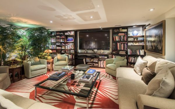 enormous media room lined with seating, huge flat screen and greenery - Massive Media Room - Jane Fonda's Hollywood Estate for Sale - Photos via RIS Media - Bill Salvatore, Arizona Elite Properties 602-999-0952 - Arizona Real Estate