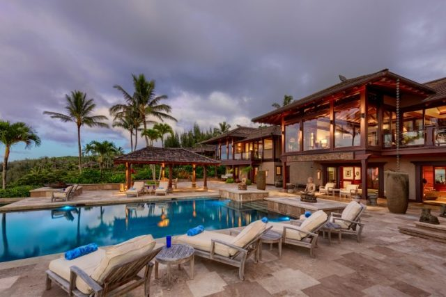 Heavy storm clouds hover over a sprawling 2-story home and very large swimming pool with decking and seating around - Most Expensive Home in Hawaii via RIS Media - Bill Salvatore, Arizona Elite Properties 602-999-0952 - Arizona Real Estate