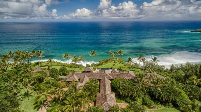 Aerial view of the pacific ocean, sky with fluffy clouds, and t-shaped home among indiginous Hawaiian greenery and trees - Most Expensive Home in Hawaii via RIS Media - Bill Salvatore, Arizona Elite Properties 602-999-0952 - Arizona Real Estate
