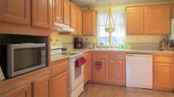 Light wood kitchen cabinets in L-shaped kitchen, light wood-laminate floor - 161 N 88th Place, Mesa AZ - Bill Salvatore, Arizona Elite Properties - Mesa AZ Homes for Sale