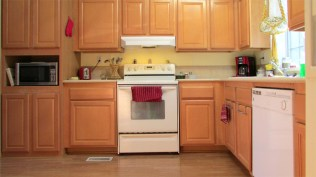 L-shaped kitchen, white stove and range-hood and countertop - White appliances - 161 N 88th Place, Mesa AZ - Bill Salvatore, Arizona Elite Properties - Manufactured Home for sale in Mesa AZ