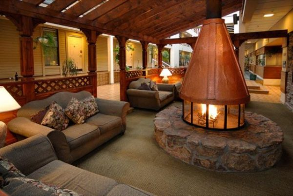 circular fireplace surrounded by glass on a circular stone hearth, with copper cone-shaped flu - Contemporary fireplaces, homes for sale with a fireplace - Bill Salvatore, Arizona Elite Properties 602-999-0952 - Arizona Homes for Sale
