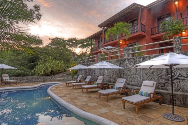 Sunset view of swimming pool, stone patio with seating and umbrellas, rear of home with balconies - Pool and patios - Mel Gibson's Costa Rica house for sale, Costa Rica Vacation property, Luxury home on Costa Rica - Bill Salvatore, Arizona Elite Properties 602-999-0952 - Costa Rica Real Estate for Sale