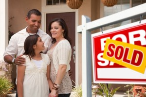 family standing beside SOLD sign in front of home - happy home sellers, happy home buyers, SOLD home - Bill Salvatore, Arizona Elite Properties 602-999-0952 - Arizona Real Estate