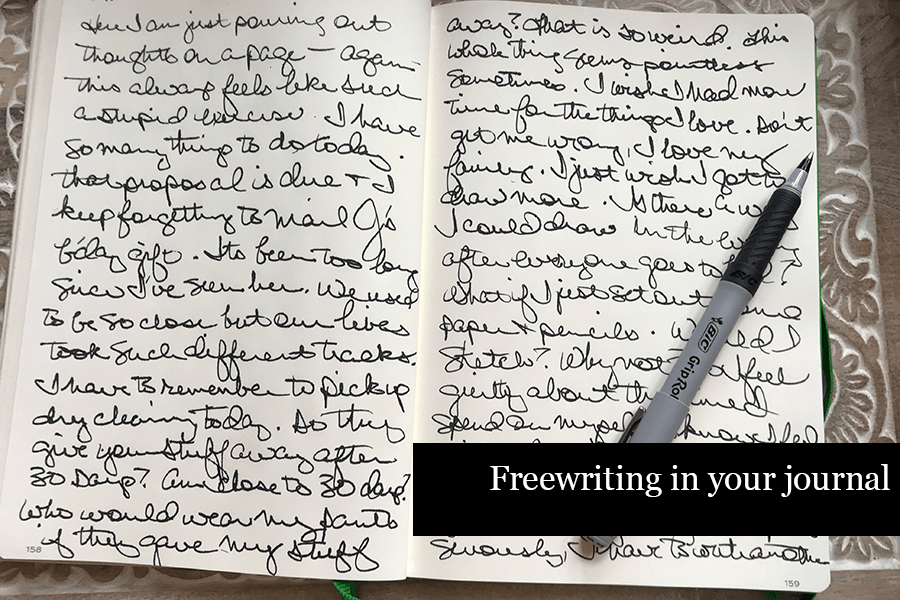 Journal with pen and freewriting across the pages. Text says: Freewriting in your journal