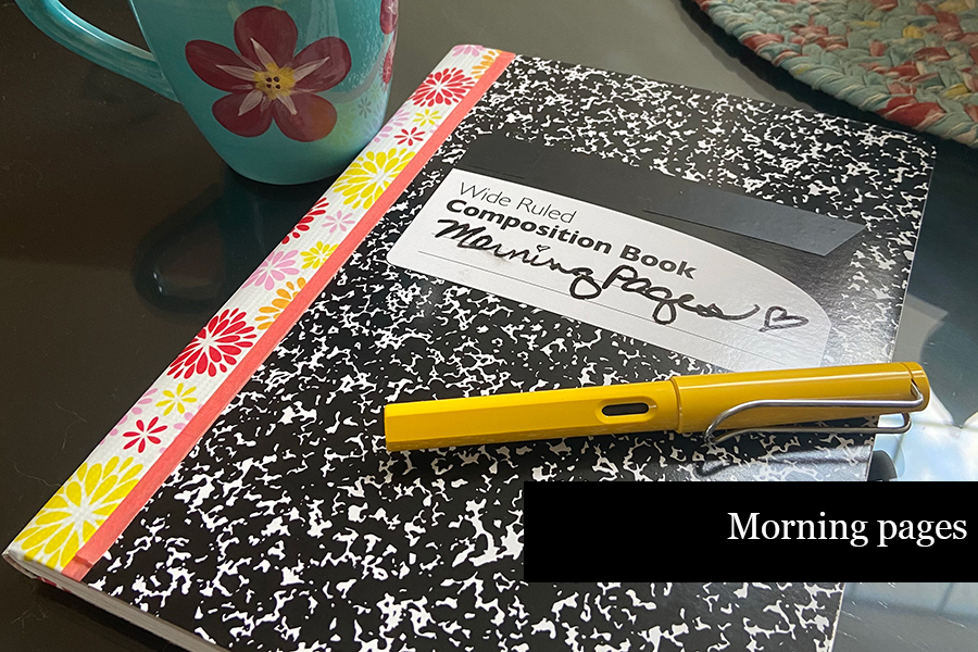 """Composition book with title """"morning pages"""" on desk with coffee cup and a pen"""