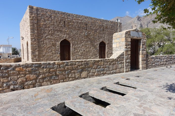 This was really special to see. This is Oman's first mosque. Islam was not always in Oman, but it started in Nizwa first, then spread across the country. You can visit this place and listen to the roaring falaj irrigation chutes slurping water down a chute. The holes allow people to wash their feet before entering the mosque.