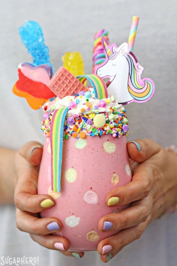 Childs hands with painted fingernails holding large pink milkshake with rainbow candy and unicorn head