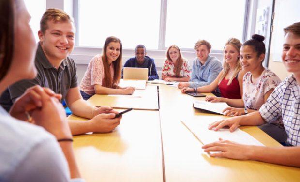 Group Of College Students Sitting At Table Having Discussion