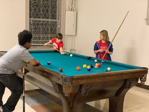 Three Youth Art Team artists playing pool.