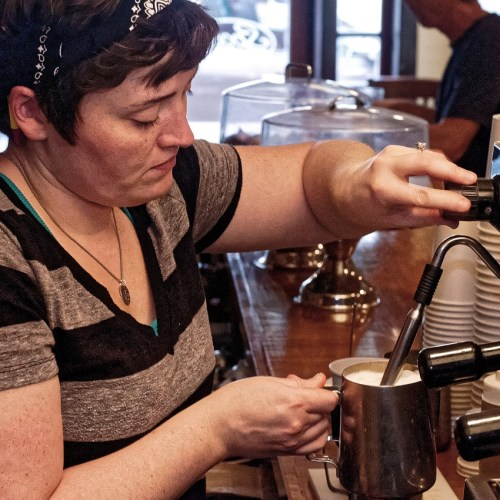 Young woman steaming milk at espresso machine