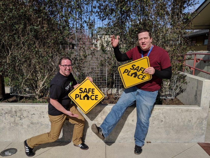 Two staff holding Safe Place signs