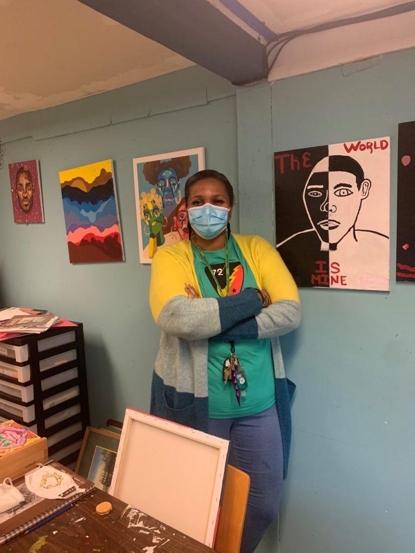 A youthcare staff member standing in front of the beautiful art work created by the youth