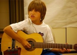 Child playing guitar and singing.