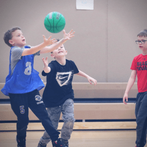 Young basketball players trying to intercept a pass.