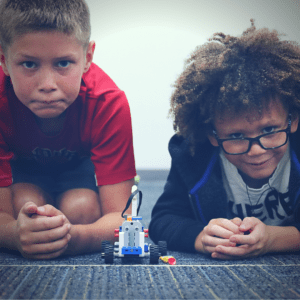 Two friends prepare to race their LEGO bricks race car.