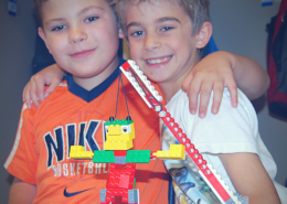 Two buddies get ready to test their waking giant LEGO project.
