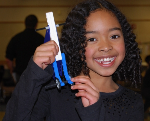 A girl holds up a LEGO project of a unique lever with wheels on it.