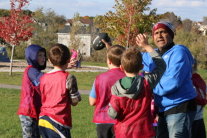 A YEL football coach directs his team.