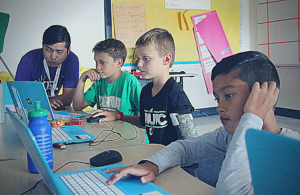A YEL Coding instructor helps his students.