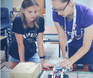 YEL Robotics teacher helps student with a challenge.