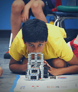 A young robotics engineer carefully places his robot for a run.