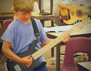 A young guitarist with an electric guitar.