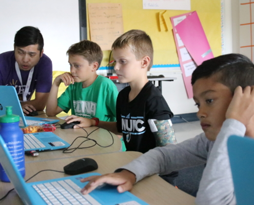YEL Coding teacher instructs students on video game creation.