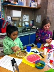 Pa Saw and Madison eat veggie stir fry with chopsticks.
