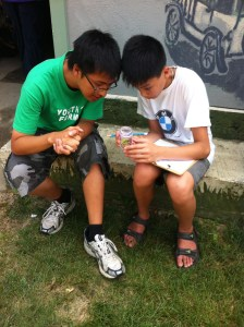 Teng and Thuan study a bug they captured in the garden.