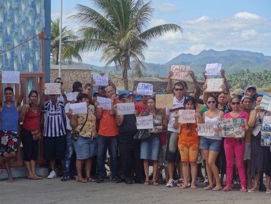 Cuba- Baracoa des personnes attendent avec panneaux pour les Casa Particular photo blog voyage tour du monde https://yoytourdumonde.fr