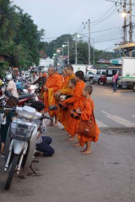Thailande: Moine bouddhiste faisant l'aumone a l'entree du marche