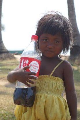 Avec mon scotter j'ai eu la malchance de faire tomber ma bouteille de coca. Une jeune locale était trop content de trouver la bouteille. Photo blog https://yoytourdumonde.fr