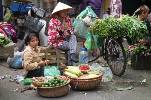 Hanoi-Vietnam: Vendeurs coiffes du chapeaux coniques vendent leurs marchandises. Regardez le velo....