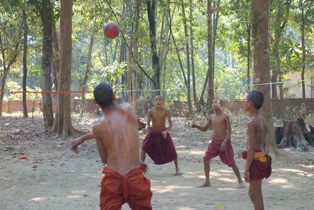Des jeunes moines bouddhistes jouent au volley ball pres d'une temple bouddhsite du coté de l'ile de l'Ogre photo voyage tour du monde https://yoytourdumonde.fr