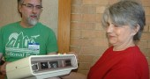 """Deborah Dillon brought her """"chirping"""" 46-year-old clock radio to last Saturday's Repair Café, a free event for repairing household items such as clothing, furniture, lamps, computers and other small electronics. Duard Headley, also pictured, was one of the volunteer """"fixers."""" The Repair Café was organized by Kat Walter of YS Time Exchange. (Photo by Audrey Hackett)"""