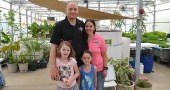 Kimball and Stephanie Osborne, with their children, Elli, left, and Alina, in the lush greenhouse at Oasis Aqua Farms in Beavercreek Township last month, before the tornado hit their property. (Photo by Megan Bachman)