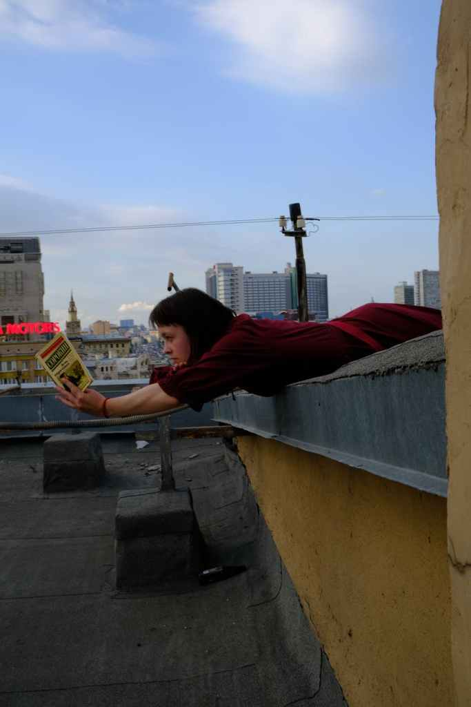 woman lying on roof edge with book