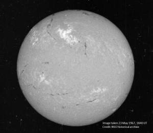 A view of the sun on May 23, 1967, in a narrow visible wavelength of light called Hydrogen-alpha. The bright region in the top center region of brightness shows the area where the large flare occurred. Credit: National Solar Observatory historical archive.
