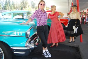 AAUW members (from left) Andrea Vetter, Janine Martin, and Fran Erickson are getting into the 50s mood, complete with bobby sox and poodle skirt at The Big A Drive-in with 50s rides provided by Roamin' Angels.