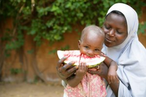 A mother holds her child while eating a slice of watermelon in Niamey the capital of Niger. Photo: UNICEF/Giacomo Pirozzi
