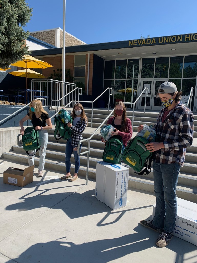 Emmalee Oistad, Taylor Demaranville, Marin Martin, Ryan Crabtree, help move CERT supplies to the classroom where training will be conducted.
