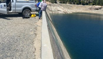 An NID crew works on the Bowman Dam on June 23. Notice the low levels of Bowman Reservoir. The dark line on the dam is the water mark.